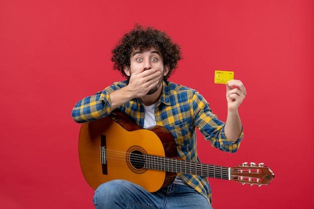 赤い壁の色のパフォーマンス拍手ミュージシャンライブコンサートバンドのお金で銀行カードを保持しているギターを持つ若い男性の正面図
