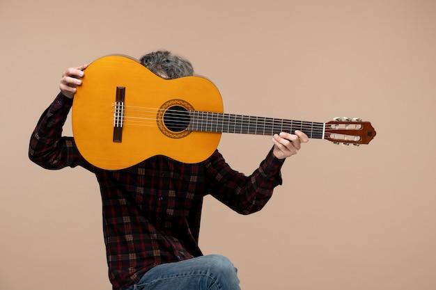 Vista frontale del giovane maschio con la chitarra sul muro rosa