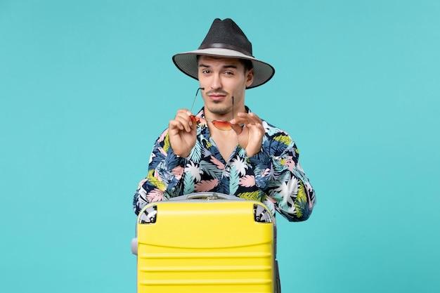 Vista frontale del giovane maschio con la sua borsa gialla che prepara per il viaggio sulla parete blu