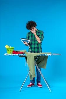 전면 보기 파란색 배경에 철을 가진 젊은 남성 인간의 깨끗한 세탁기 컬러 하우스