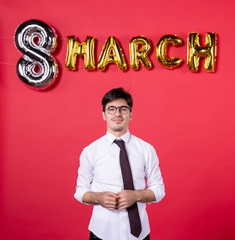 正面図赤い背景色の3月の装飾を持つ若い男性女性現在の休日官能的な情熱女性の日の流行
