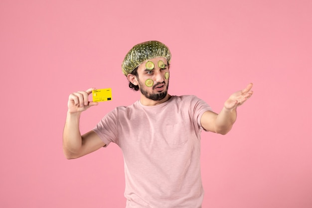 Front view young male with mask on his face holding bank card on pink background