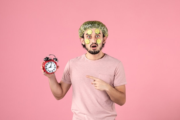 Front view young male with mask on his face holding clock on pink background