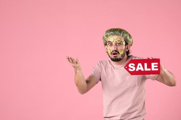 Vista frontale giovane maschio con maschera sul viso tenendo la targhetta di vendita su sfondo rosa