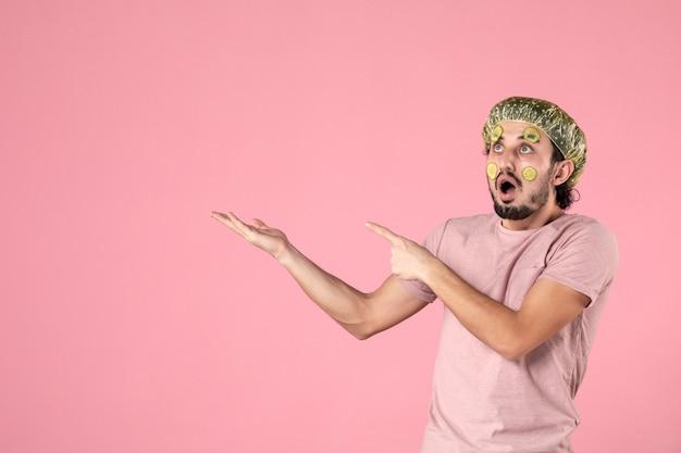 Vista frontale giovane maschio con maschera sul viso su sfondo rosa