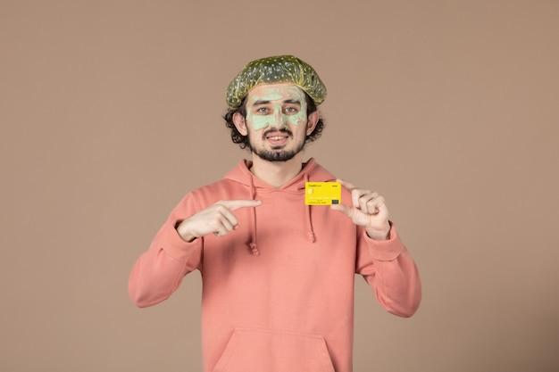 Вид спереди молодой мужчина с маской на лице, держащий кредитную карту на коричневом фоне, салон терапии волос, уход за кожей лица, спа