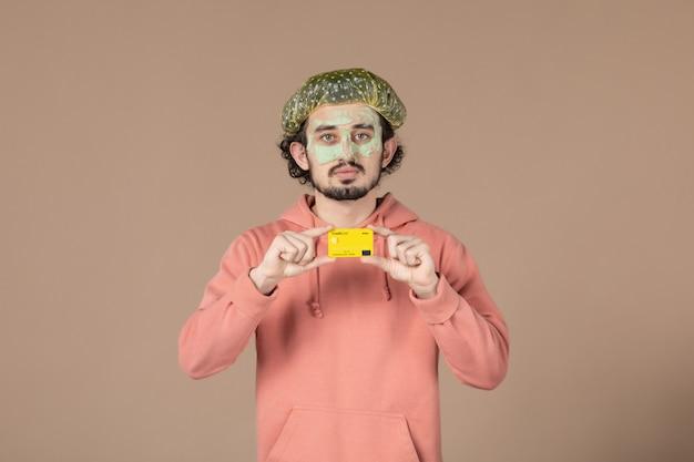 Вид спереди молодой мужчина с маской на лице, держащий кредитную карту на коричневом фоне, уход за волосами, салон красоты, уход за кожей лица, спа