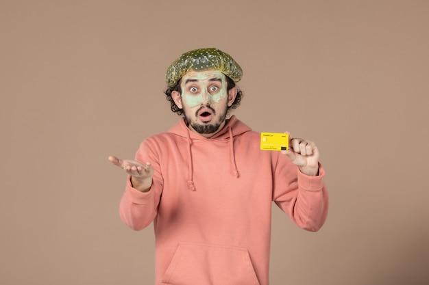 Вид спереди молодой мужчина с маской на лице, держащий кредитную карту на коричневом фоне, денежная терапия, уход за кожей лица, уход за телом, спа