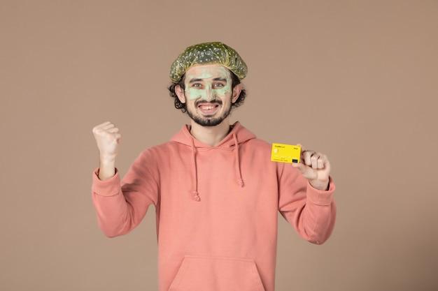 Вид спереди молодой мужчина с маской на лице, держащий кредитную карту на коричневом фоне, денежная терапия, салон по уходу за кожей, уход за лицом, спа
