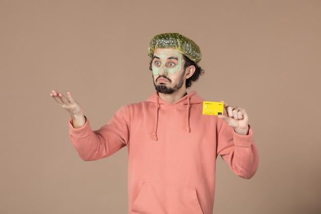 Вид спереди молодой мужчина с маской на лице, держащий кредитную карту на коричневом фоне, денежная терапия, салон ухода за кожей лица, уход за телом, цвет спа
