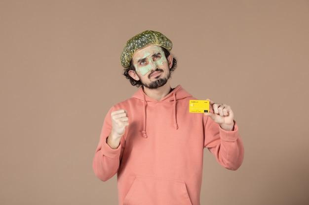 Вид спереди молодой мужчина с маской на лице, держащий кредитную карту на коричневом фоне, денежная терапия, салон по уходу за кожей, уход за кожей лица, уход за телом, спа цвета