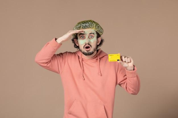 Вид спереди молодой мужчина с маской на лице, держащий кредитную карту на коричневом фоне, денежная терапия, салон по уходу за кожей лица, уход за телом, спа