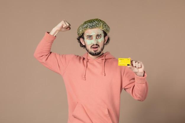 Вид спереди молодой мужчина с маской на лице, держащий кредитную карту на коричневом фоне, денежная терапия, салон по уходу за кожей лица, уход за телом