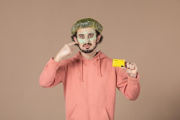 Вид спереди молодой мужчина с маской на лице, держащий кредитную карту на коричневом фоне, денежная терапия, салон ухода за кожей лица, спа