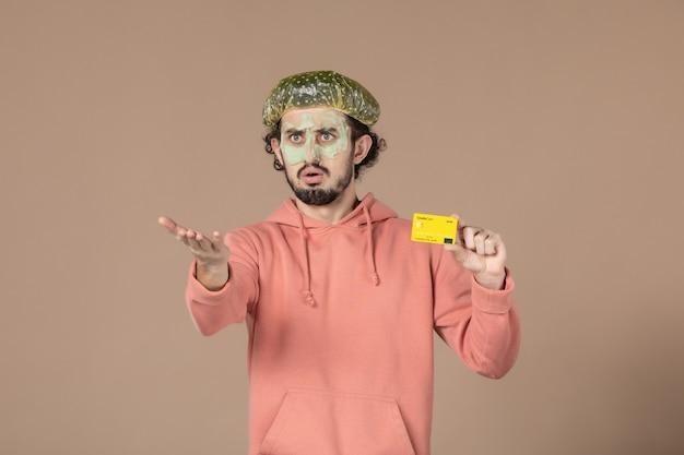 Вид спереди молодой мужчина с маской на лице, держащий кредитную карту на коричневом фоне, денежная терапия, салон ухода за кожей, уход за кожей, спа