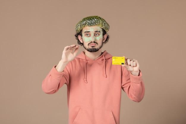 Вид спереди молодой мужчина с маской на лице с кредитной картой на коричневом фоне салон деньги цветотерапия уход за кожей лица уход за телом спа