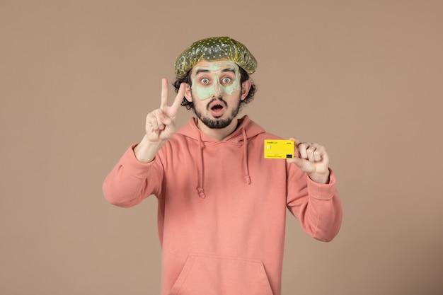Вид спереди молодой мужчина с маской на лице с кредитной картой на коричневом фоне салон денежная терапия цветной уход за кожей лица уход за телом спа
