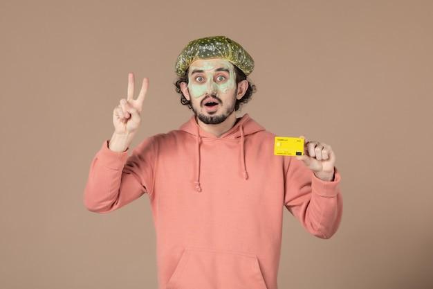 Вид спереди молодой мужчина с маской на лице, держащий кредитную карту на коричневом фоне, салон, денежная терапия, уход за кожей лица, спа