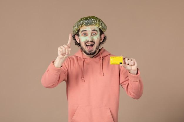 Вид спереди молодой мужчина с маской на лице, держащий кредитную карту на коричневом фоне, салон, денежная терапия, уход за кожей, цвет кожи лица, уход за телом, спа