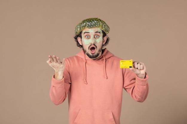 Вид спереди молодой мужчина с маской на лице, держащий кредитную карту на коричневом фоне, салон, денежная терапия, уход за кожей, уход за лицом, уход за телом, спа