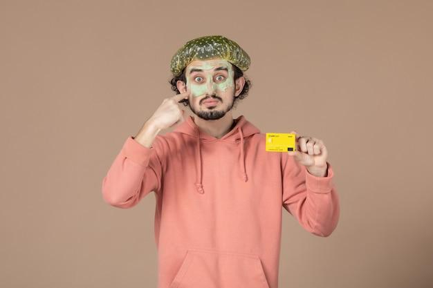 Вид спереди молодой мужчина с маской на лице, держащий кредитную карту на коричневом фоне, салон, денежная терапия, уход за кожей, уход за кожей лица, уход за телом, цвет спа