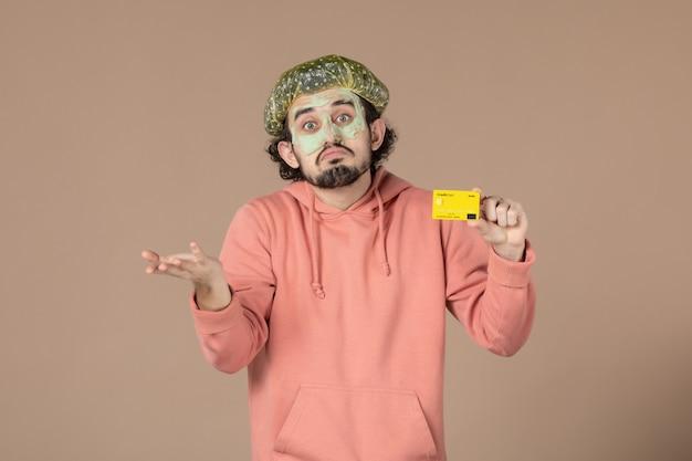 Вид спереди молодой мужчина с маской на лице, держащий кредитную карту на коричневом фоне, салон, денежная терапия, уход за кожей, уход за кожей лица, уход за телом, спа цвета