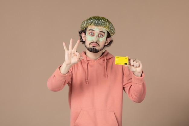 Вид спереди молодой мужчина с маской на лице держит кредитную карту на коричневом фоне салон деньги терапия уход за кожей лица уход за телом спа фото