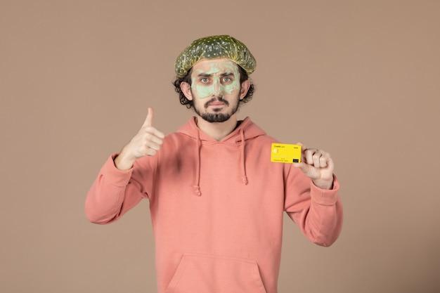 Вид спереди молодой мужчина с маской на лице с кредитной картой на коричневом фоне салон денежная терапия уход за кожей лица уход за телом спа