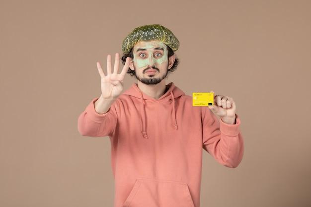 Вид спереди молодой мужчина с маской на лице держит кредитную карту на коричневом фоне салон денежная терапия уход за кожей лица уход за телом