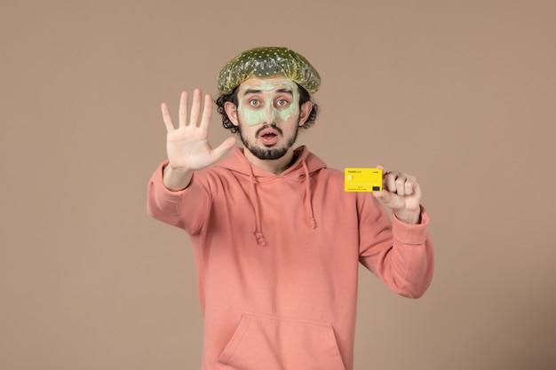Вид спереди молодой мужчина с маской на лице держит кредитную карту на коричневом фоне салон денежная терапия уход за кожей лица спа спа
