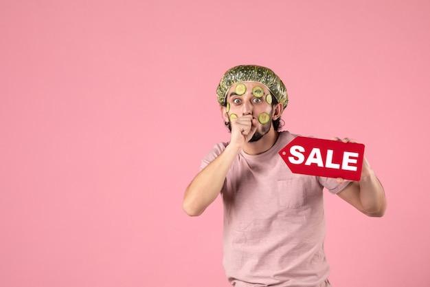 분홍색 배경에 판매 명판을 들고 그의 얼굴에 마스크와 전면보기 젊은 남성