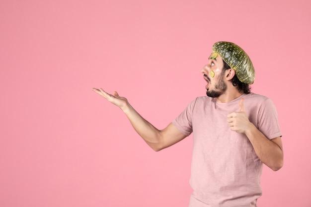 분홍색 배경에 그의 얼굴에 마스크와 전면보기 젊은 남성