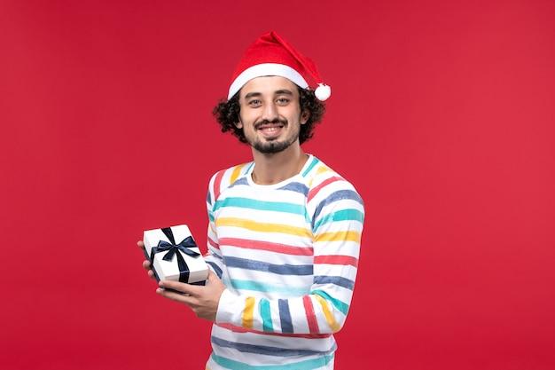 Вид спереди молодой мужчина с новогодним подарком и настроением на красной стене праздник красный новый год