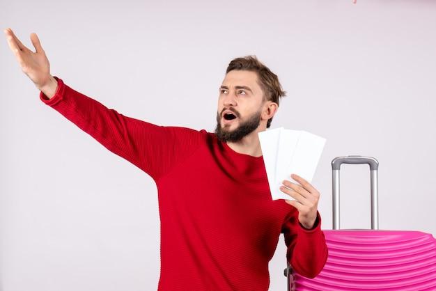 Вид спереди молодой мужчина с розовой сумкой и держащий билеты на самолет на белой стене путешествие рейс поездка туристический отдых эмоции фото