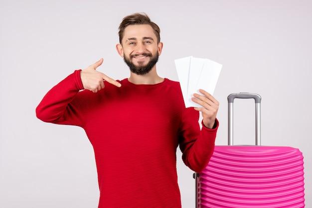 Вид спереди молодой мужчина с розовой сумкой и держащий билеты на самолет на белой стене путешествие рейс поездка отпуск эмоция фото турист