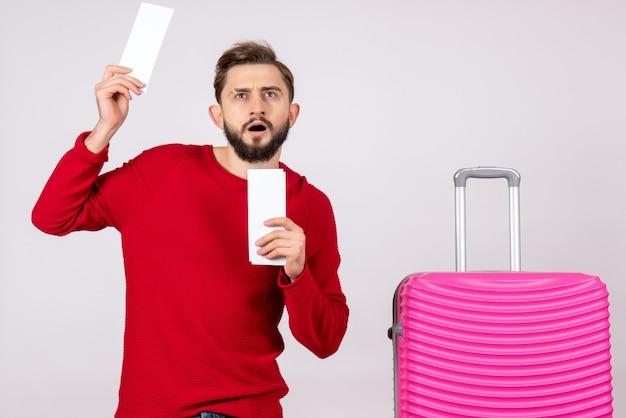 ピンクのバッグと白い壁の旅の色の休暇の飛行航海夏の観光客のチケットを保持している正面図若い男性