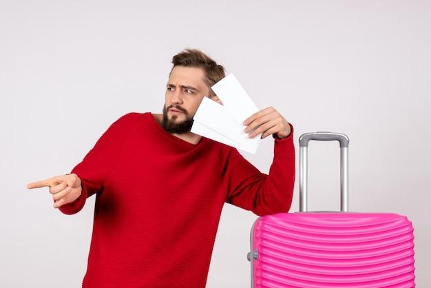 Вид спереди молодой мужчина с розовой сумкой и держит билеты на белой стене, цветная поездка, отпуск, рейс, путешествие, туристы
