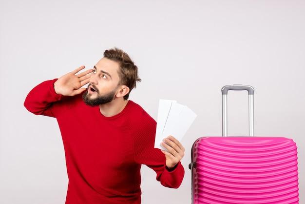 분홍색 가방과 흰 벽 컬러 여행 휴가 항공편 항해 관광에 티켓을 들고 전면보기 젊은 남성