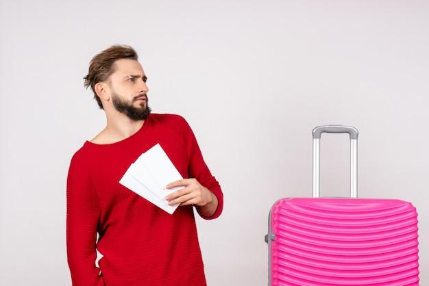Вид спереди молодой мужчина с розовой сумкой и держащий билеты на белой стене, цветная поездка, путешествие, туристические каникулы