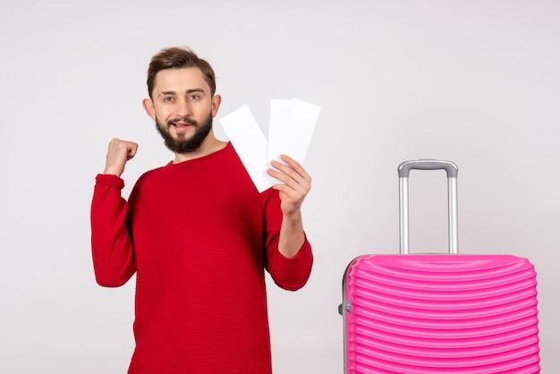 ピンクのバッグと白い壁のチケットを保持している正面図若い男性航海飛行カラー旅行観光休暇感情写真