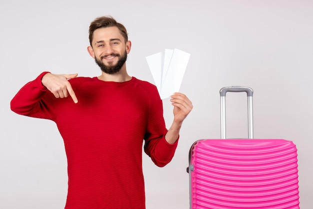Вид спереди молодой мужчина с розовой сумкой и держащий билеты на белой стене рейс цветное путешествие туристический отдых эмоции фото