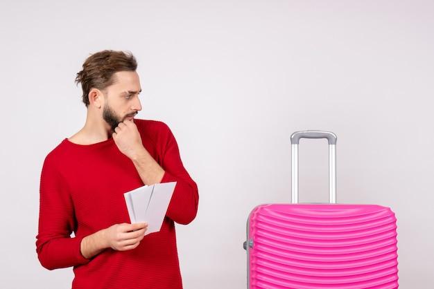 분홍색 가방과 흰 벽 항해 비행 컬러 여행 관광 휴가 사진 감정에 티켓을 들고 전면보기 젊은 남성