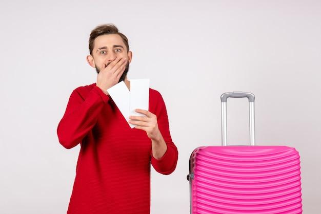 Вид спереди молодой мужчина с розовой сумкой и держит билеты на белой стене рейс рейс цвет поездка туристы отпуск эмоция фото