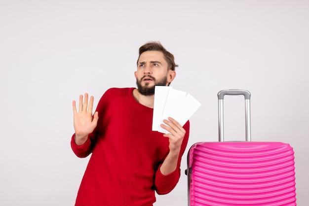 분홍색 가방과 흰 벽 항해 항공편 컬러 여행 관광 휴가 사진 감정에 티켓을 들고 전면보기 젊은 남성
