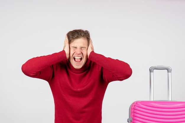 Vista frontale del giovane maschio con borsa rosa che copre le orecchie sul muro bianco