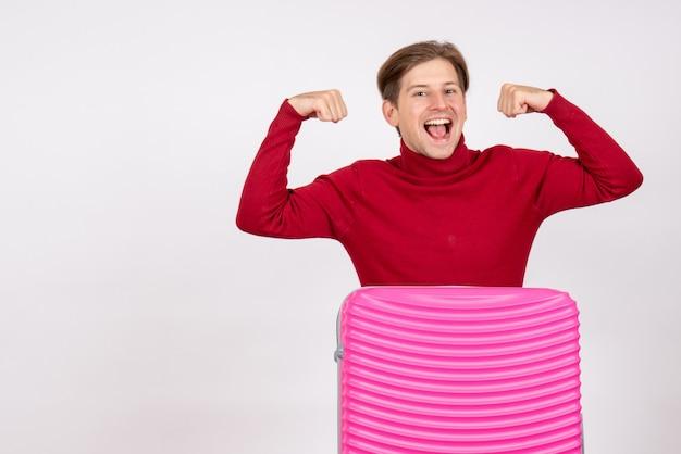 Vista frontale del giovane maschio con borsa rosa che flette sul muro bianco