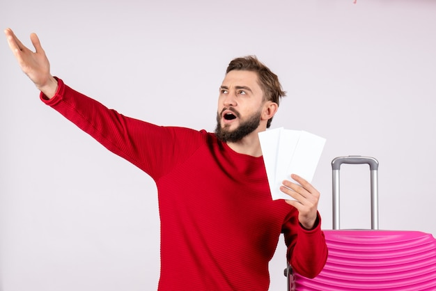 Front view young male with pink bag and holding plane tickets on white wall voyage flight trip tourist vacation emotions photo