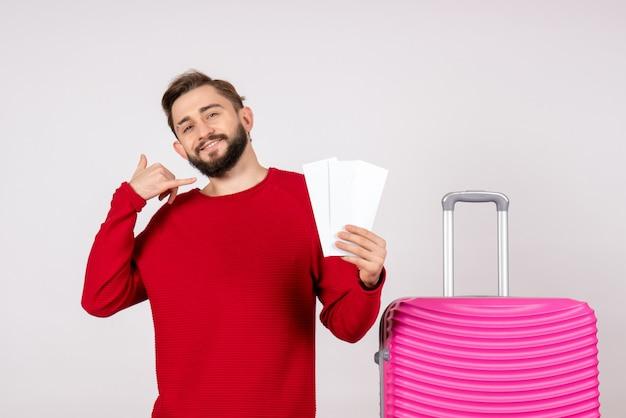 Giovane maschio di vista frontale con il sacchetto rosa e che tiene i biglietti sul turista di volo di vacanza di viaggio di colore della parete bianca