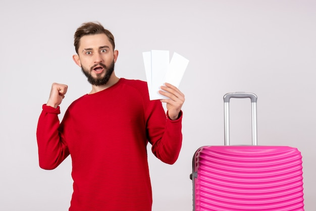 Front view young male with pink bag and holding tickets on white wall trip color vacation flights voyage summer tourist
