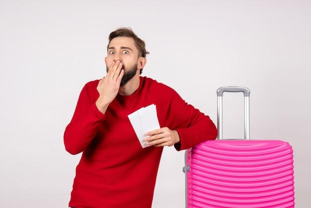 Giovane maschio di vista frontale con borsa rosa e che tiene i biglietti sulla foto turistica di viaggio di colore di volo di viaggio della parete bianca